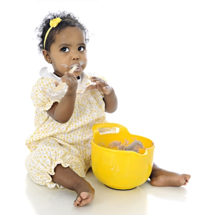 An adorable baby girl eating pudding from a bowl